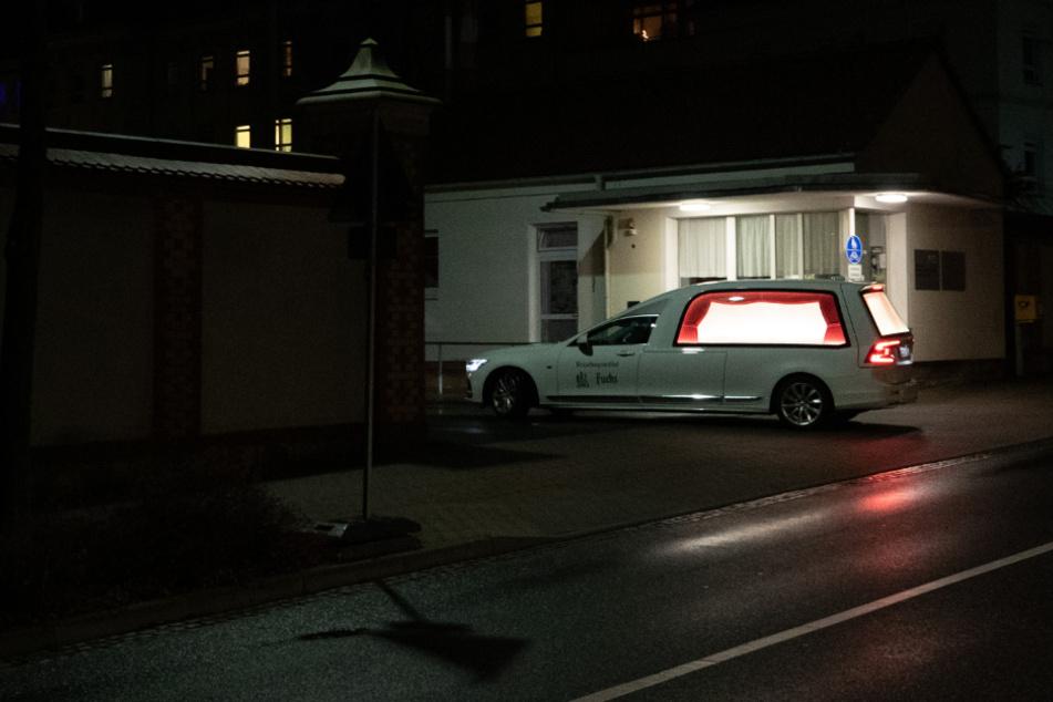 Ein Leichenwagen fährt am Abend in die Einfahrt des Klinikum Oberlausitz Bergland.