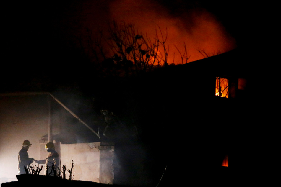 Feuerwehrleute stehen unweit eines brennenden Gebäudes. Das Großfeuer zerstörte am Weihnachtsabend dutzende Häuser.