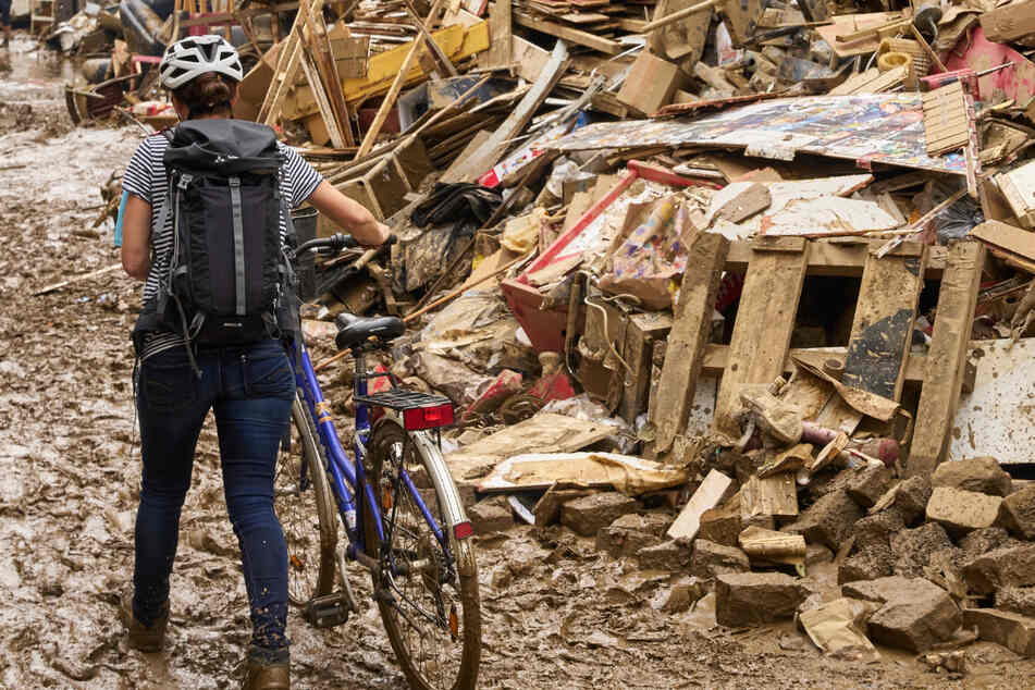 Eine Frau schiebt in Ahrweiler ihr Fahrrad durch den Schlamm. Anwohner versuchen, ihre Häuser vom Schlamm zu befreien und unbrauchbares Mobiliar nach draußen zu bringen.
