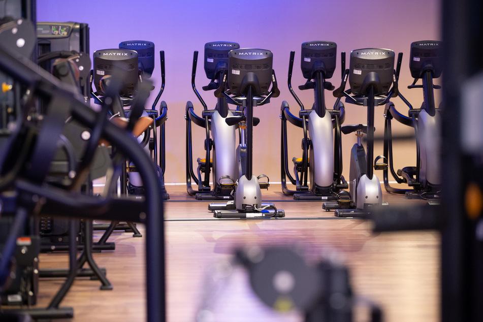 Unbenutzte Trainingsgeräte stehen in einem geschlossenen Fitnessstudio.