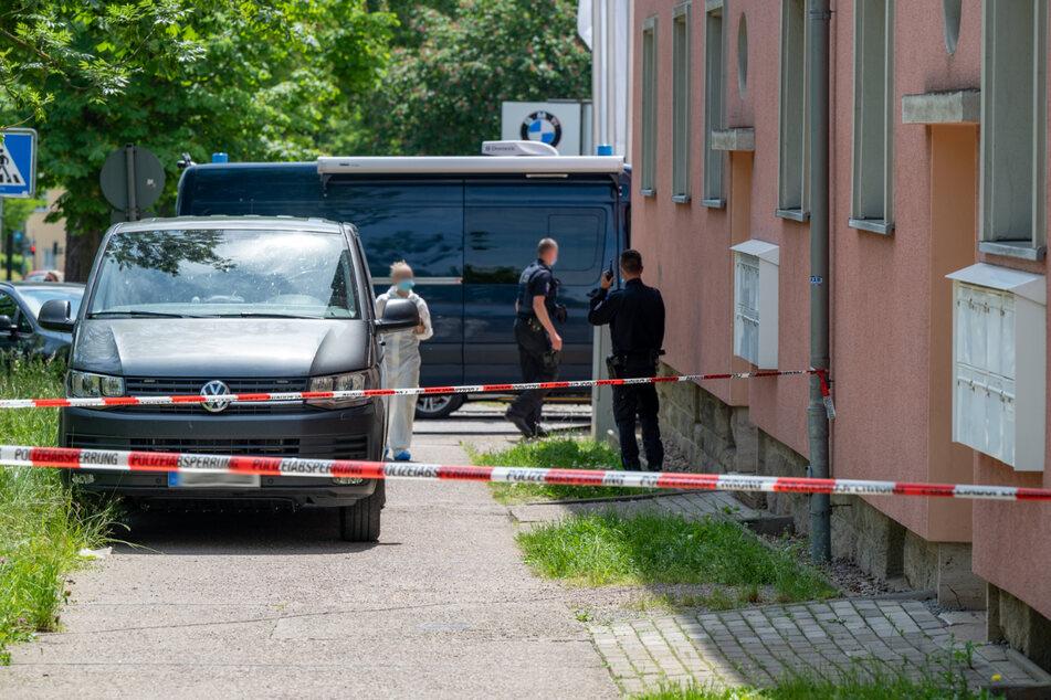 Einsatzkräfte stehen vor dem abgesperrten Mehrfamilienhaus. In einer Wohnung wurde am Dienstag eine tote Person gefunden.