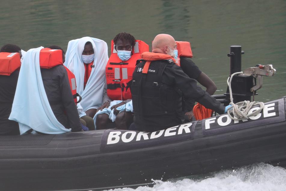 Gerettete Männer sitzen in einem Schlauchboot.
