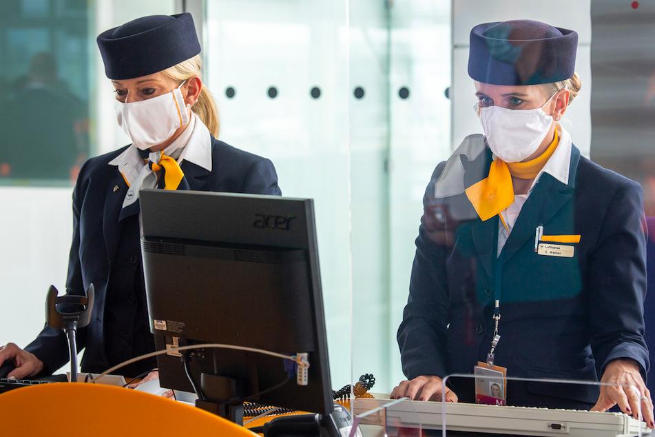 Zwei Lufthansa-Mitarbeiterinnen mit Mund-Nasen-Sschutzmaske und hinter Plexiglasscheiben fertigen am Flughafen-Terminal 2 die Gäste für den Flug in die USA ab.