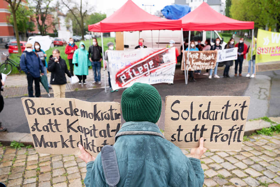 Teilnehmer einer Kundgebung des Deutschen Gewerkschaftsbundes (DGB) stehen anlässlich des Internationalen Tags der Pflege mit Transparenten auf der Blasewitzer Straße.