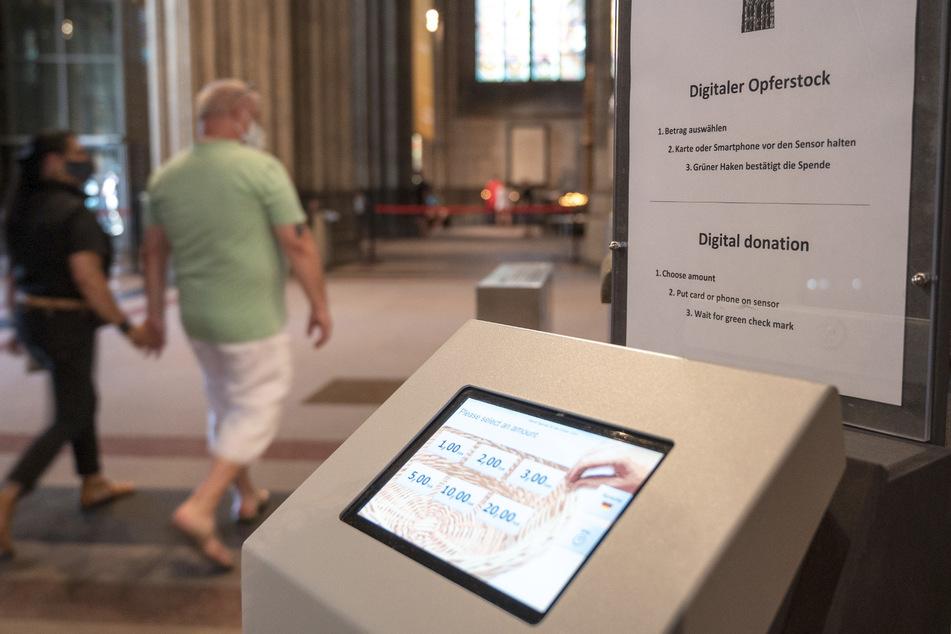 Ein digitaler Opferstock steht im Eingangsbereich des Kölner Doms.