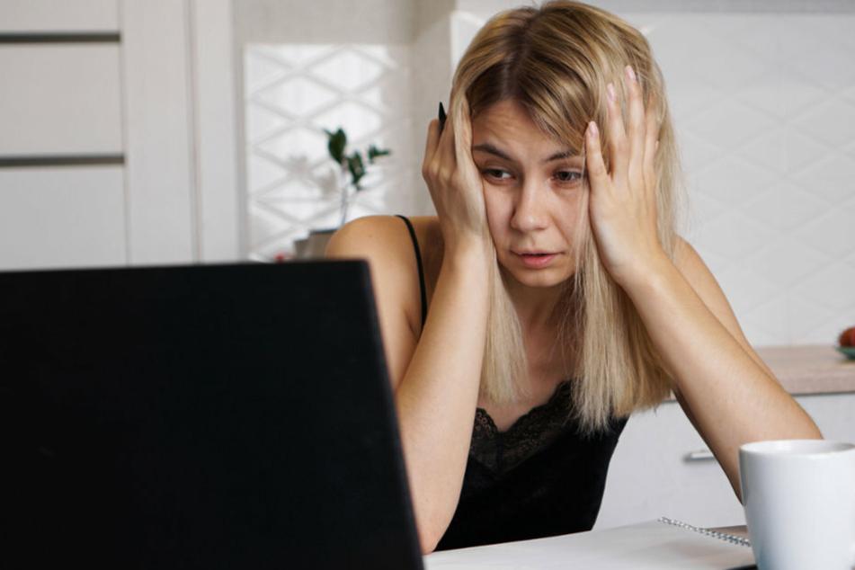 Eine Frau sitzt völlig verzweifelt vor ihrem Rechner. (Symbolbild)