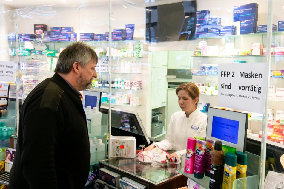 Eine Apothekerin berät einen Kunden hinter einer Plexiglasscheibe.