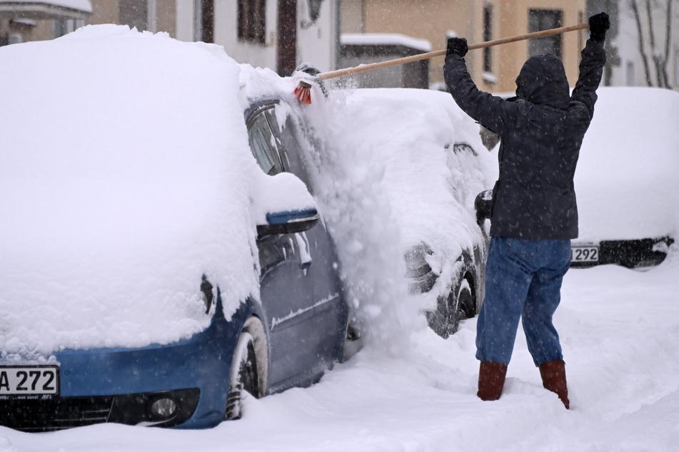 In Kassel musste eine Frau ihr Auto von den vielen Schneemassen befreien.