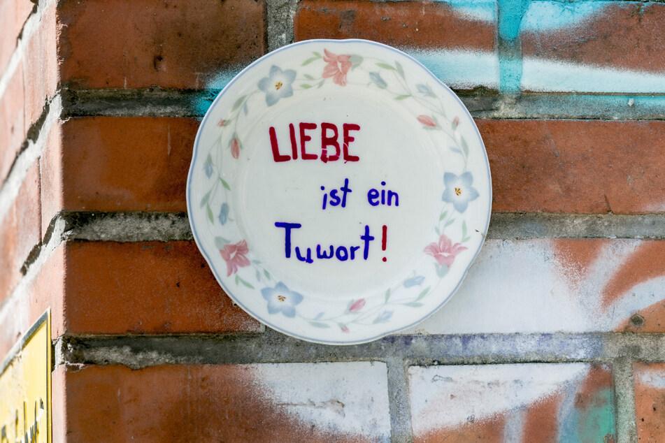 """Dieser Teller mit der Aufschrift """"LIEBE ist ein Tuwort"""" hängt an einer Wand im Stadtteil Eimsbüttel."""