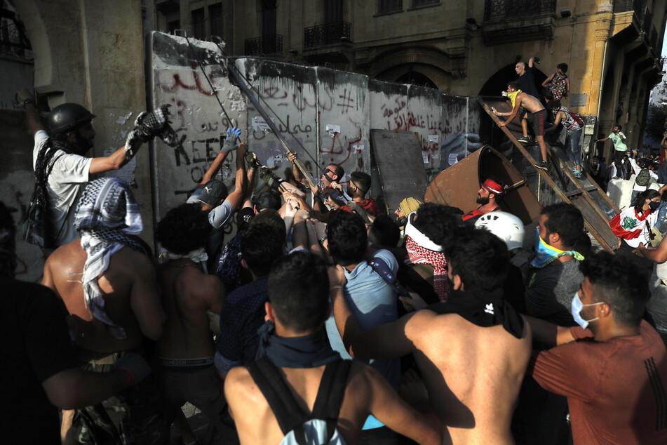 Demonstranten versuchen bei einem regierungskritischen Protest, die Betonmauer zu entfernen, die von den Sicherheitskräften errichtet wurde, um die Demonstranten daran zu hindern, das Parlamentsgebäude zu erreichen.