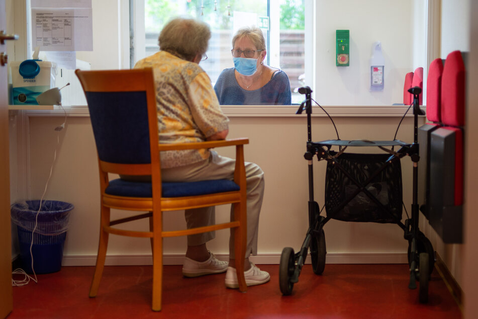 Eine Besucherin unterhält sich im Besuchsraum eines Alteheimes mit ihrer Angehörigen.