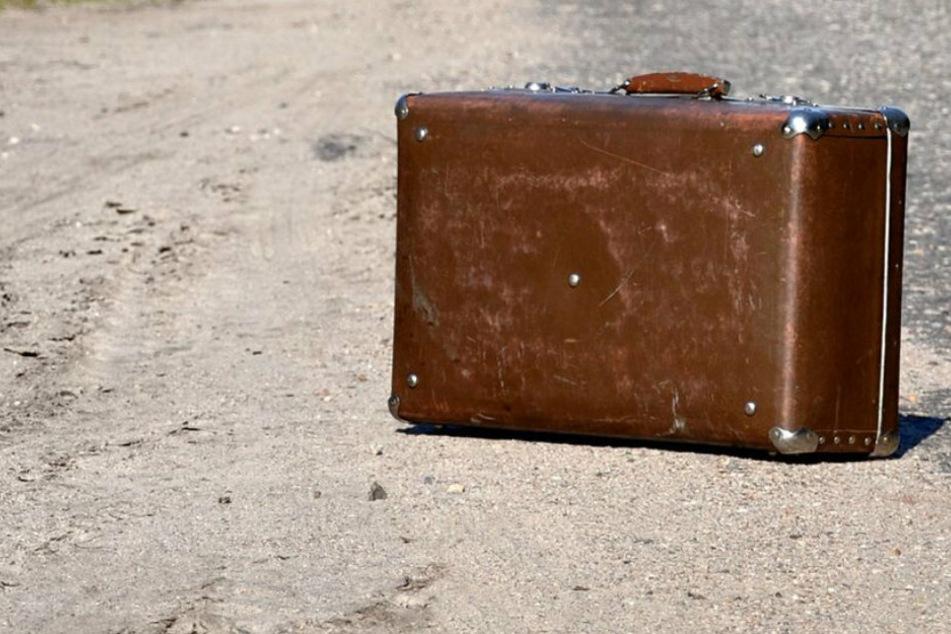 Ein Koffer steht an einem verstaubten Straßenrand (Symbolbild).