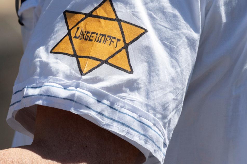"""""""Ungeimpft"""" steht auf einem nachgebildeten Judenstern am Arm eines Mannes."""