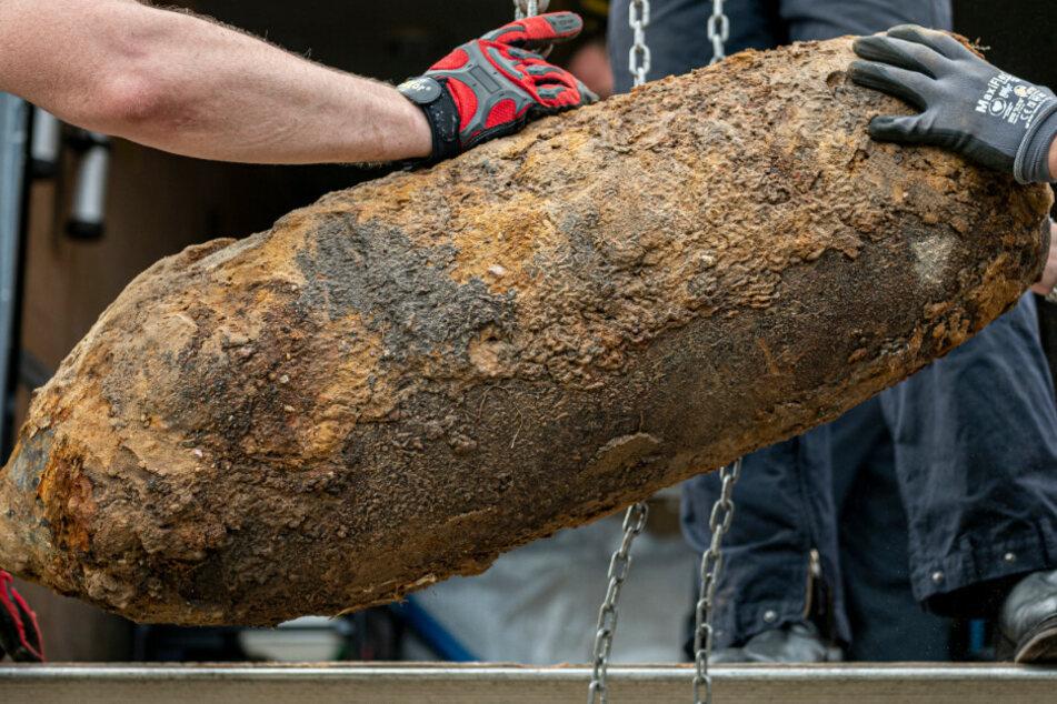 Eine entschärfte Weltkriegsbombe wird von Einsatzkräften mit einem Kran verladen. (Symbolbild)
