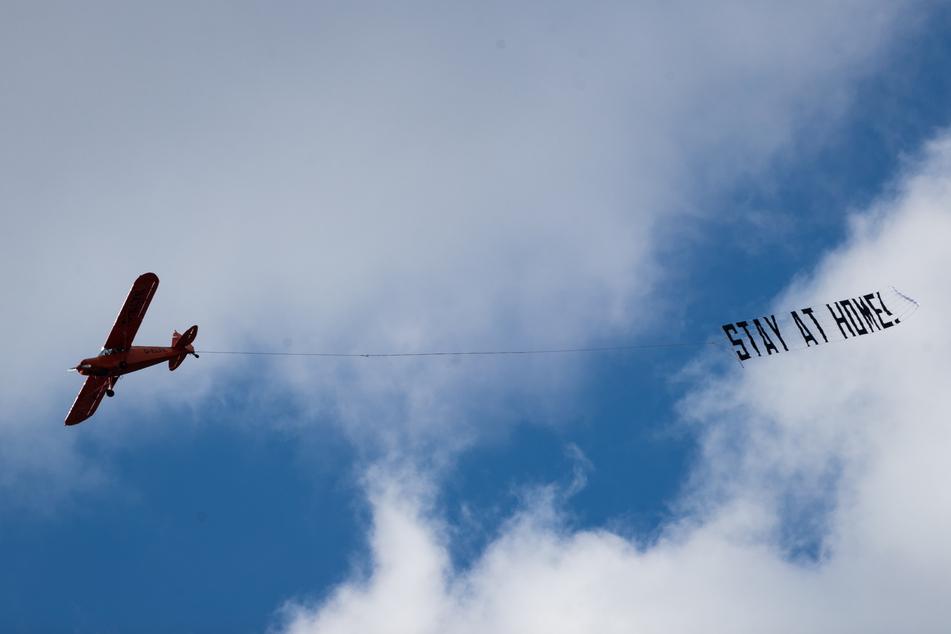 """Ein kleines Flugzeug fliegt mit einem Banner mit der Aufschrift """"Stay at Home!"""" (Bleibt zu Hause!) über Hamburg."""