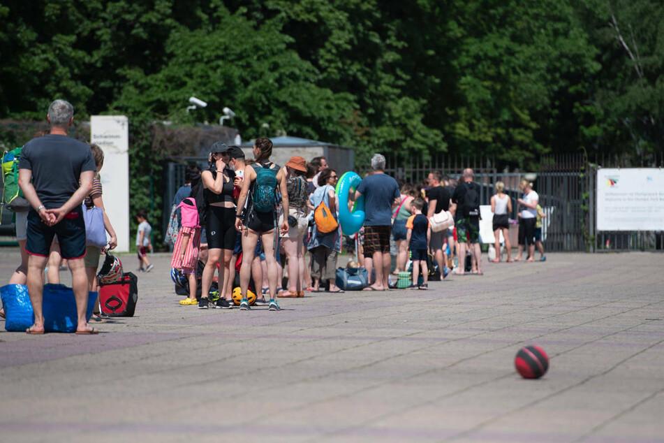 Menschen stehen bei warmem Wetter in einer Schlange vor dem Eingang zum Olympiabad in Niederfinow. Im Zuge der Corona-Lockerungen haben die Freibäder in Brandenburg bei warmem Sommerwetter einen guten Zulauf verzeichnet.