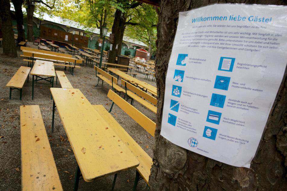 Ein Hinweisschild mit den Corona-Verhaltensregeln hängt am Baum eines leeren Biergartens in München.