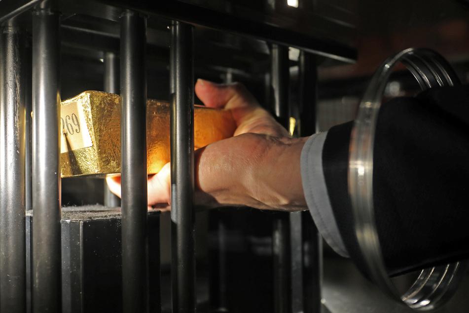 Teil der Ausstellung in Bonn: Ein Mann hebt einen 12,5 Kilo schweren Goldbarren der Deutschen Goldreserve, der in einer Vitrine gesichert ist, an.