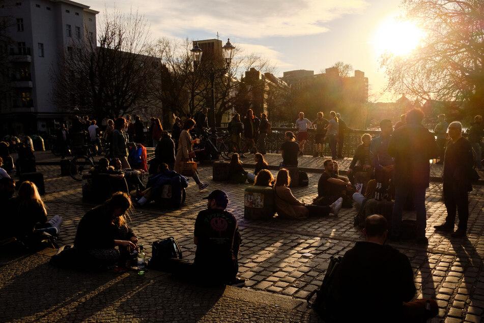 Zahlreiche Menschen sitzen, ohne Schutzmasken und zum Teil ohne den vorgeschriebenen Mindestabstand einzuhalten, im Licht der untergehenden Sonne auf der Admiralbrücke, einem beliebten Treffpunkt junger Menschen im Stadtteil Kreuzberg.