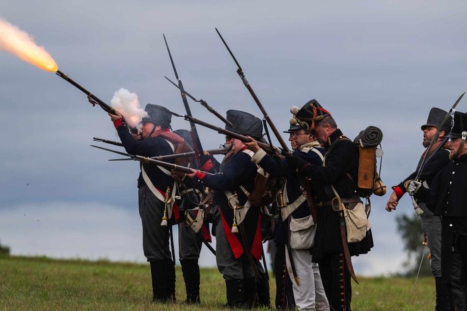 Als Soldaten verkleidete Darsteller feuern auf dem nachgestellten Schlachtfeld mit ihren Waffen.
