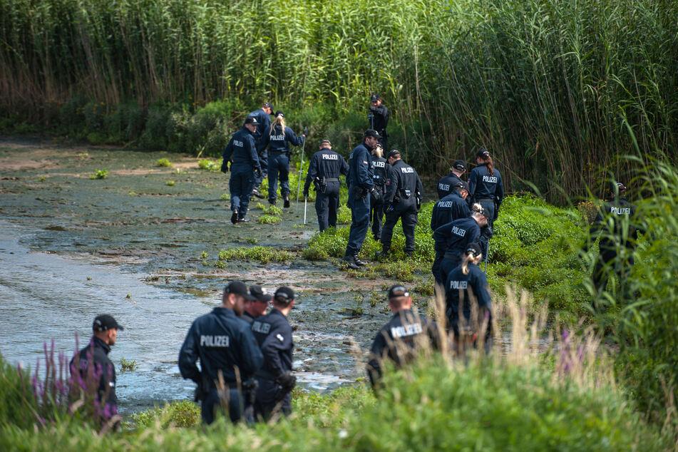 Polizisten suchen am Elbufer nach einer vermissten Frau und ihrer Tocher.