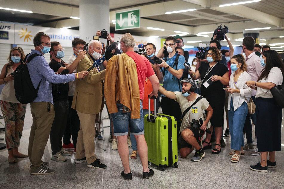 Ein Fluggast (M) vom morgendlichen TUI-Flug Düsseldorf-Mallorca wird am Flughafen Son Sant Joan von Journalisten interviewt.
