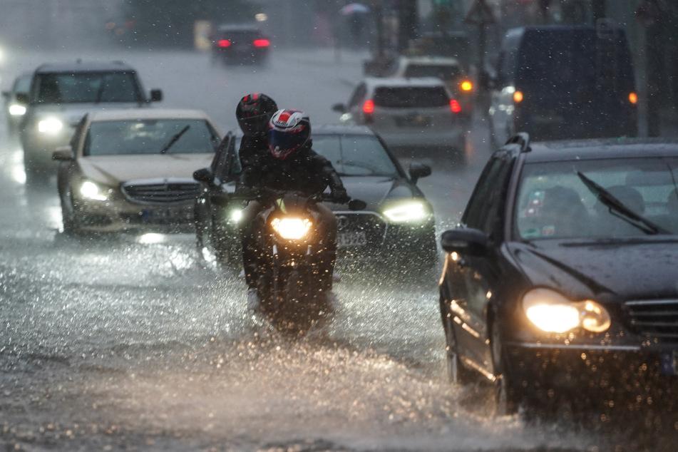 Autos und Motorräder fahren bei starkem Regen über die überflutete Friedrichstraße in Berlin-Mitte.
