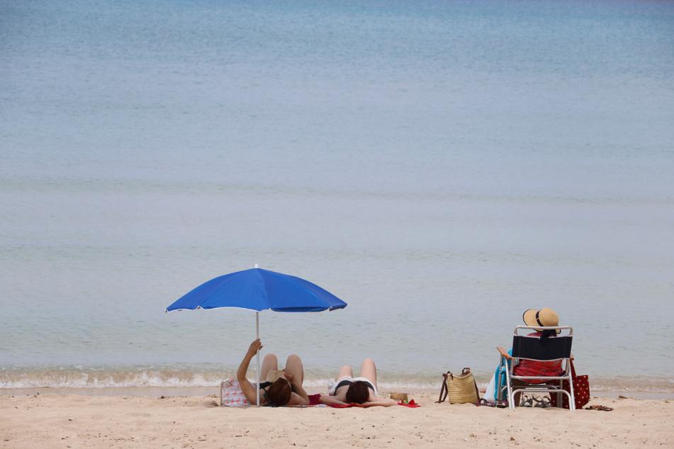 25.05.2020, Spanien, Palma de Mallorca: Menschen sonnen sich am Strand von Arenal. Nach einer mehr als zweimonatigen Zwangsschließung wegen der Corona-Pandemie haben die Urlaubsinsel und viele andere Regionen Spaniens am Montag ihre Strände wieder geöffnet. Foto: Clara Margais/dpa +++ dpa-Bildfunk +++