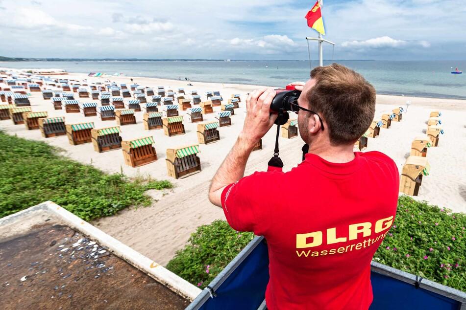 Ein Rettungsschwimmer der Deutsche Lebens-Rettungs-Gesellschaft (DLRG) betrachtet von einem Beobachtungsturm aus den Ostseestrand.