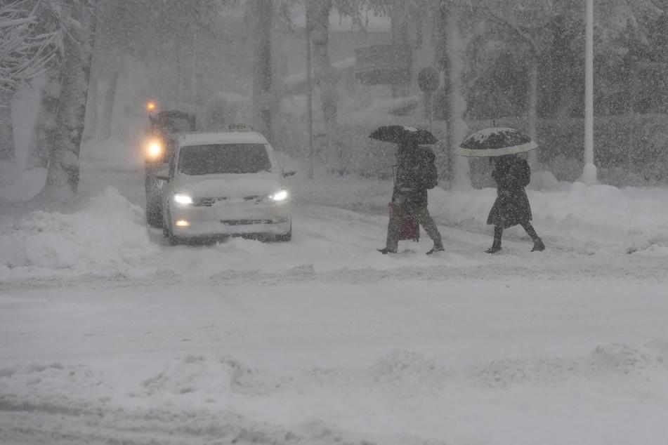 Fußgänger und Autos kämpfen sich am Donnerstag im bayrischen Garmisch-Partenkirchen durch den Schnee.