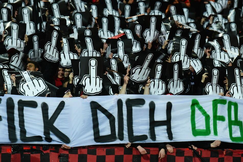 """Nürnberger Fans halten Schilder mit Mittelfingern in die Höhe und zeigen ein langes Banner mit der Aufschrift """"Fick Dich DFB""""."""