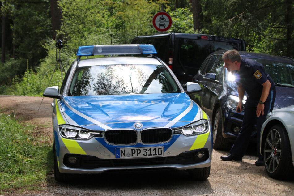 Polizisten stehen auf einem Waldweg im Nürnberger Land, in dessen Nähe ein Pilzsammler eine Leiche entdeckt hat. (Archiv)