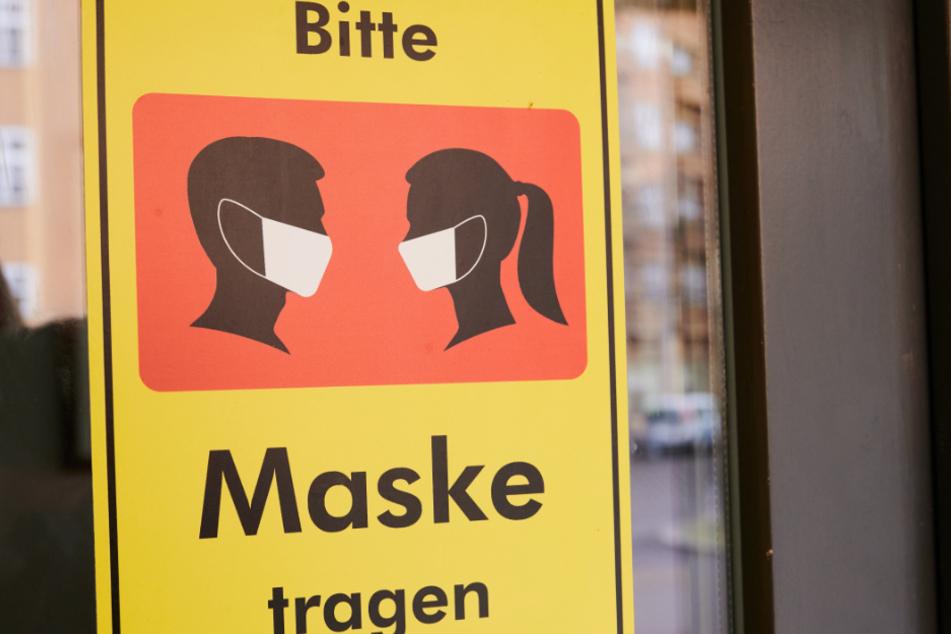 """Auf einem Gebäude steht """"Bitte Maske tragen"""". In Görlitz hat eine Frau die Maskenpflicht missachtet."""