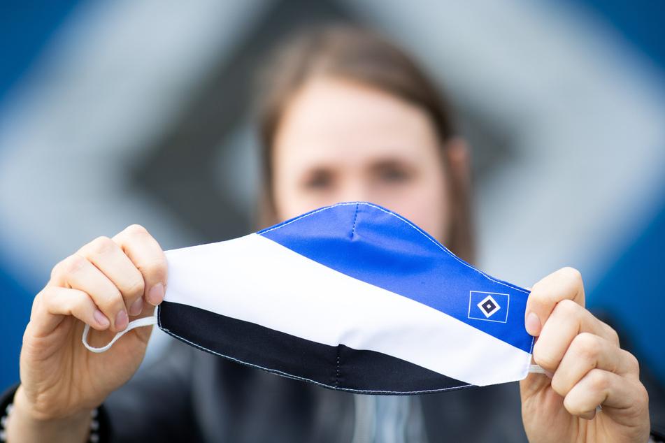 Eine Mitarbeiterin des Hamburger SV hält eine Mund-Nasen-Schutzmasken in der Hand.