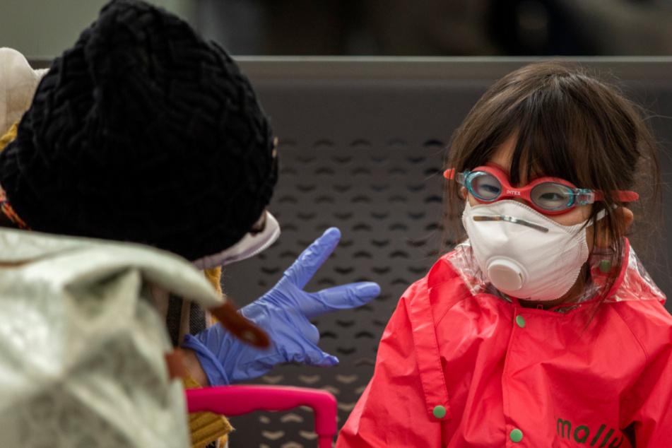 Eine Mutter mit Schutzhandschuhen spielt mit ihrer Tochter, die eine Atemschutzmaske und eine Schwimmbrille trägt, am Flughafen Josep Tarradellas Barcelona-El Prat.