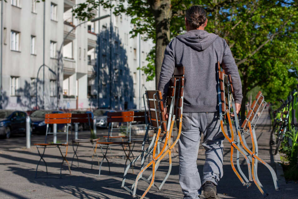 Ein Mann stellt Stühle an einem Café am Weigandufer auf. Mit dem Kaffee auf der Terrasse oder dem Weizen im Biergarten - ab Freitag heißen Gaststätten, Clubs und Freibäder in Berlin nach monatelangen coronabedingten Schließungen wieder Gäste willkommen.