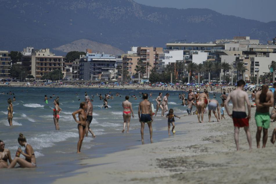 Touristen sonnen sich am Strand von Arenal in Spanien, Palma de Mallorca. Die Maskenpflicht wurde im gesamten Land erheblich gelockert.
