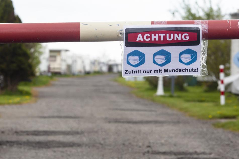 """Ein Schild mit der Aufschrift """"Achtung. Zutritt nur mit Mundschutz!"""" hängt an einer Schranke eines Campingplatzes in Nordfriesland."""