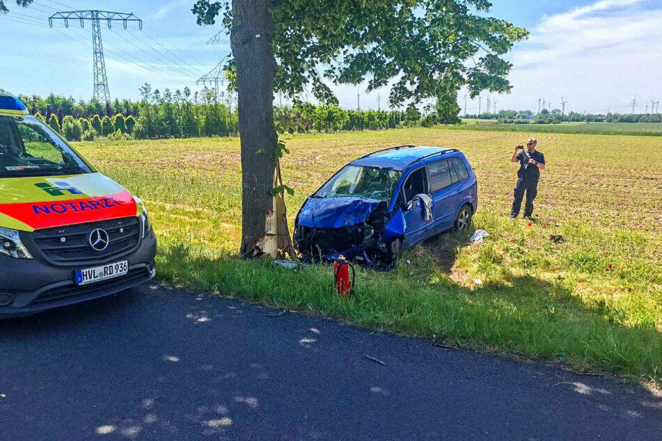 Ein Notarztfahrzeug steht auf der Straße vor dem Unfallauto.