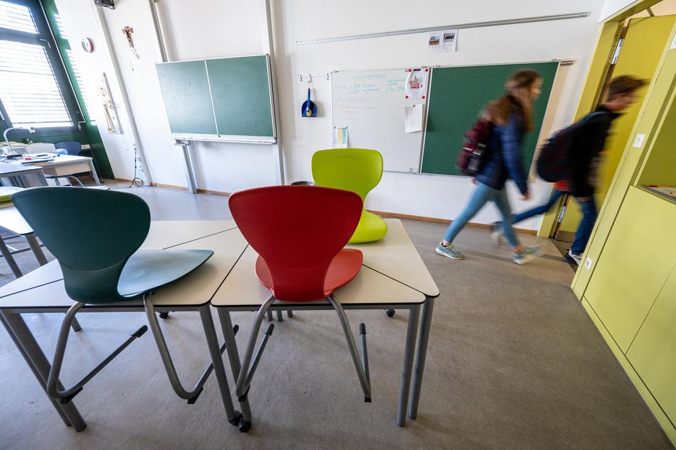 Schüler gehen nach Unterrichtsschluss aus einem Klassenzimmer.