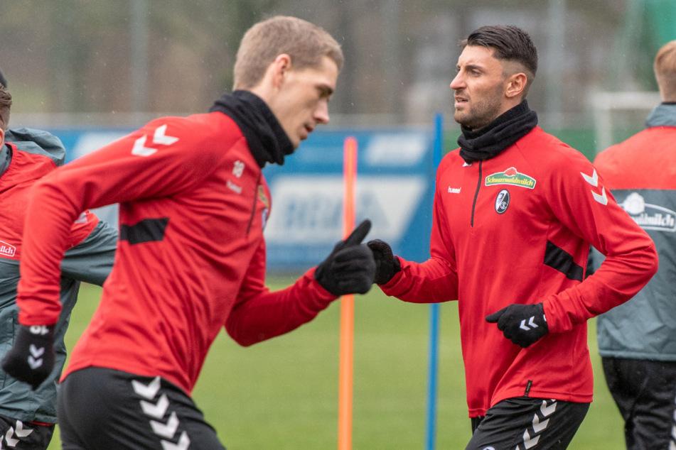 Vincenzo Grifo vom SC Freiburg (r) rennt mit Nils Petersen (l) beim Training über den Platz.