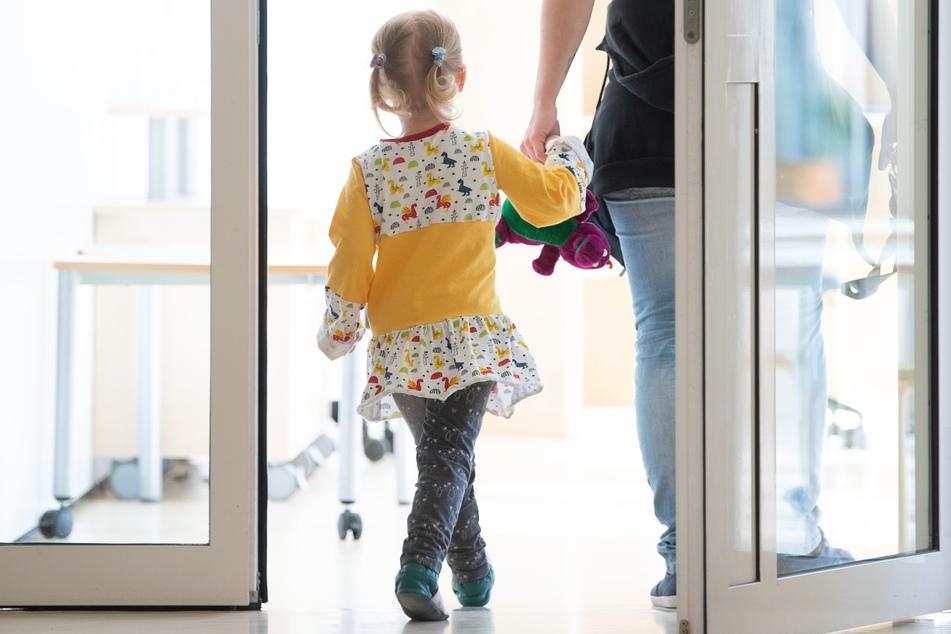 Ein Kind geht mit einer Erzieherin durch einen Kindergarten.