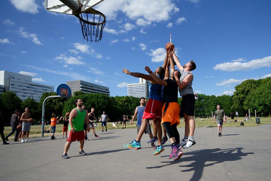 Eine Gruppe Männer spielt in einem Park Streetball.