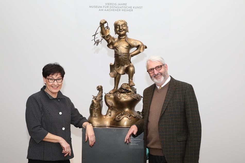 """Das Sammlerehepaar Schürzeberg vor der Skulptur des daoistischen Unsterblichen Liu Hai"""" im Museum für Ostasiatische Kunst Köln."""