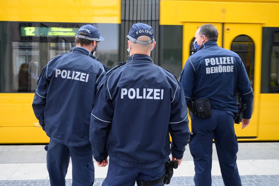 Polizisten und ein Ordnungsamtbeamter stehen bei einer Kontrolle der Einhaltung der Maskenpflicht im öffentlichen Personennahverkehr an einer Haltestelle vor einer Straßenbahn.