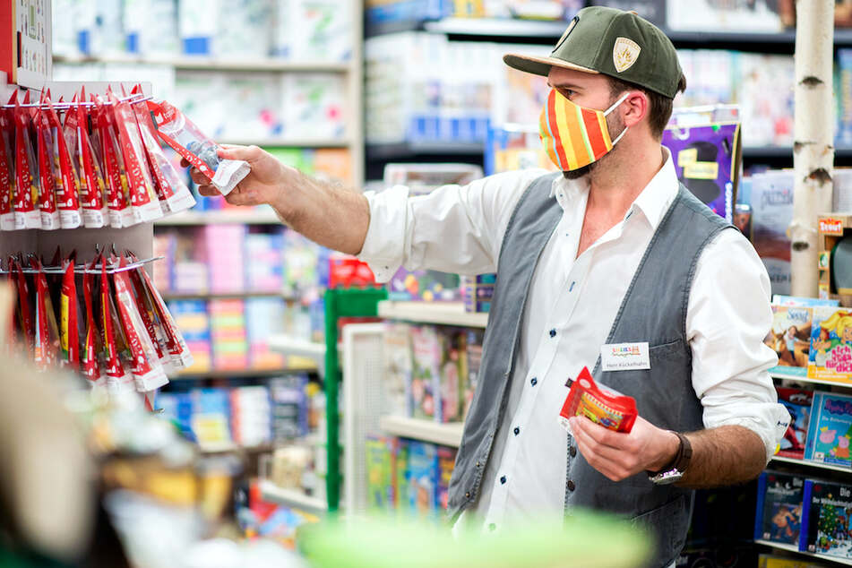 Ein Mann räumt Spielwaren in ein Regal ein, während er eine Stoffmaske im Gesicht trägt.