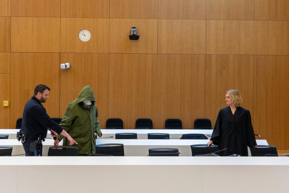 Ein 56 Jahre alter, wegen sexuellen Kindesmissbrauchs, angeklagter Mann (M) wird zu Prozessbeginn am Landgericht München II in den Saal geführt. Rechts steht seine Anwältin Anja Kollmann.