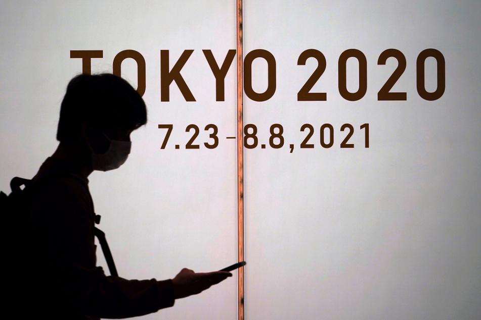 Ein Mann mit Mund-Nasen-Schutz geht in Tokio vor einer Werbung für die Olympischen Spiele 2021 entlang.