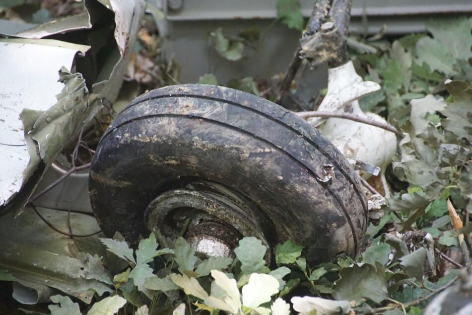 Teile des Flugzeuges liegen auf dem bewachsenen Waldboden.