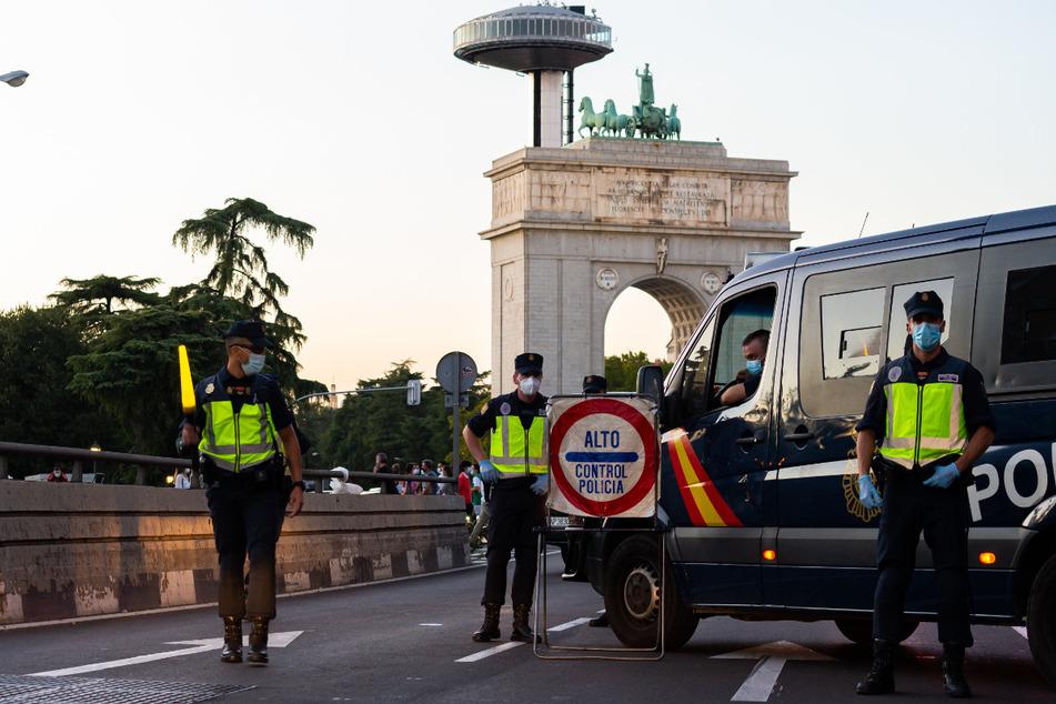 Polizisten stehen an einem Kontrollpunkt in Madrid. Die Justiz hat die umstrittene Zwangsabriegelung des Corona-Hotspots Madrid durch die spanische Zentralregierung gekippt.
